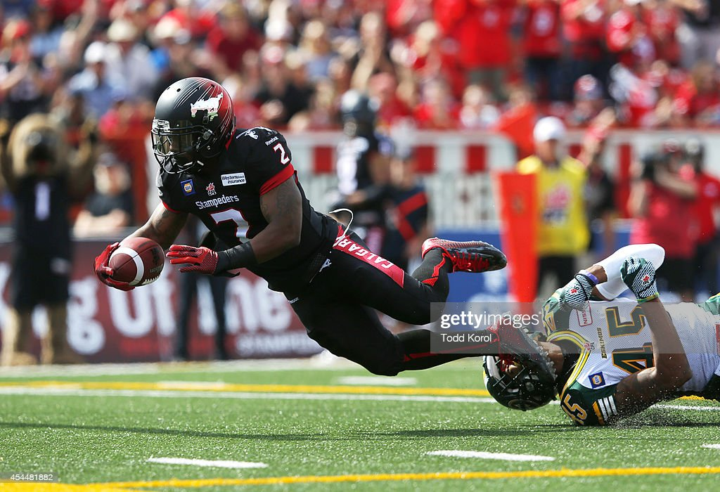 Jock Sanders #2 of the Calgary Stampeders is tackled by <a gi-track='captionPersonalityLinkClicked' href=/galleries/search?phrase=Dexter+McCoil&family=editorial&specificpeople=6233971 ng-click='$event.stopPropagation()'>Dexter McCoil</a> #45 of the Edmonton Eskimos in the first half of their CFL football game September 1, 2014 at McMahon Stadium in Calgary, Alberta, Canada. (Photo by Todd Korol/Getty Images