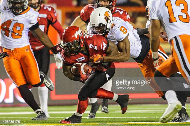 Jock Sanders of the Calgary Stampeders runs with the ball against Bo Lokombo of the BC Lions during a CFL game at McMahon Stadium on September 27...