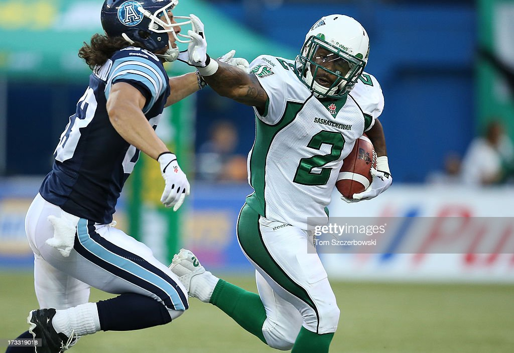 Jock Sanders #2 of the Saskatchewan Roughriders returns the ball during CFL game action against Julian Feoli-Gudino #83 of the Toronto Argonauts on July 11, 2013 at Rogers Centre in Toronto, Ontario, Canada.