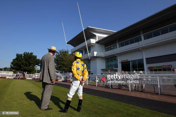 A jockey and trainer in the parade ring at Epsom Downs prior to the Download Epsom's Android Or iPhone App Now Handicap