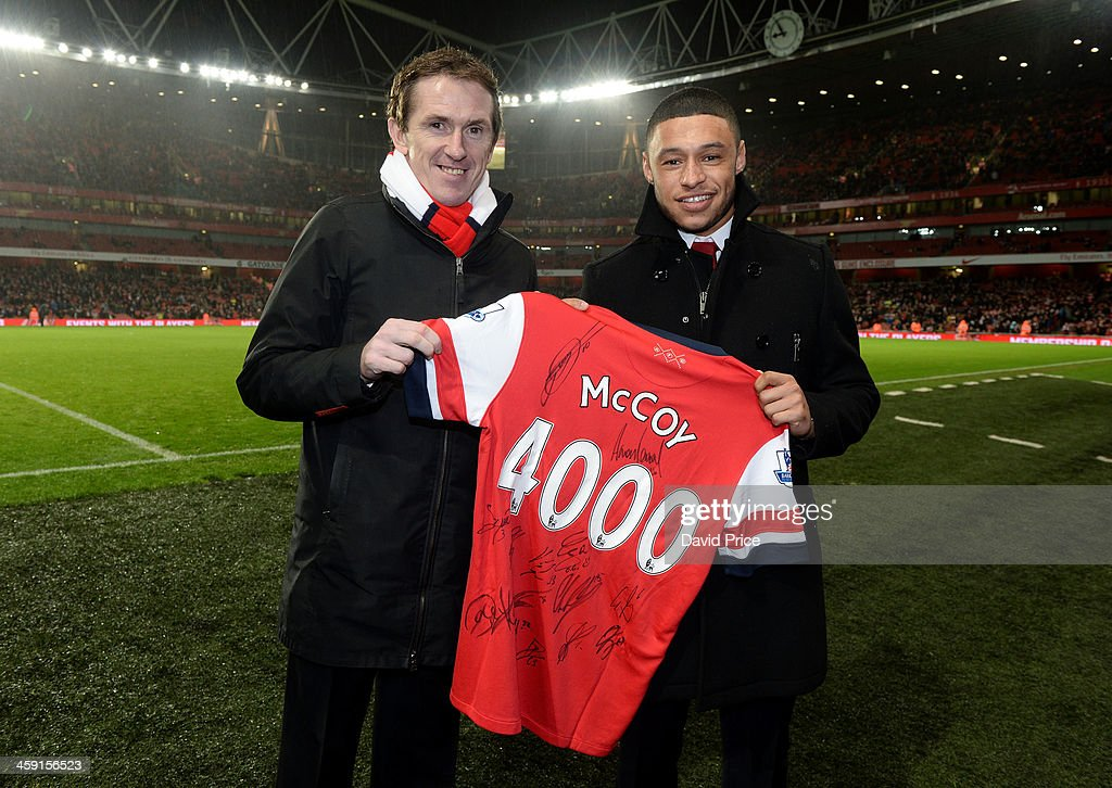 Jockey AP McCoy is presented with a signed shirt by Alex Oxlade-Chamberlain of Arsenal at half time during the match between Arsenal and Chelsea in the Barclays Premier League at Emirates Stadium on December 23, 2013 in London, England.