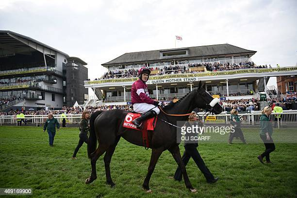 Jockey AP McCoy riding 'Don Cossack' walks to the Parade Ring having won 'The Betfred Melling Steeple Chase' on Ladies Day of the Grand National...