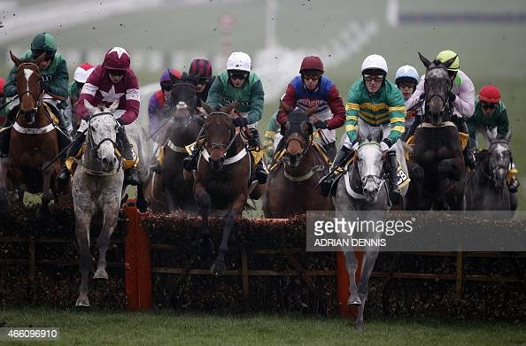 Jockey AP McCoy riding Hargam jumps a fence during the JCB Triumph Hurdle Race on the final day of the Cheltenham Festival horse racing meeting at...