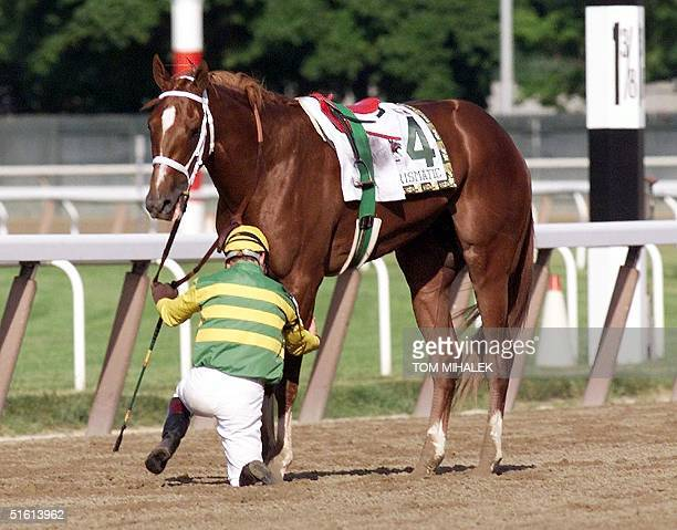 Jockey Chris Antley checks the leg of Charismatic after falling off the horse just past the finish line during the 131st running of the Belmont...