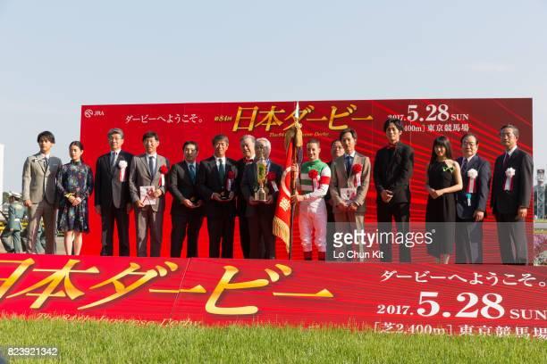 Jockey Christophe Lemaire trainer Kazuo Fujisawa and representative of Carrot Farm Fujiya Takahashi celebrate after Rey de Oro winning the Tokyo...
