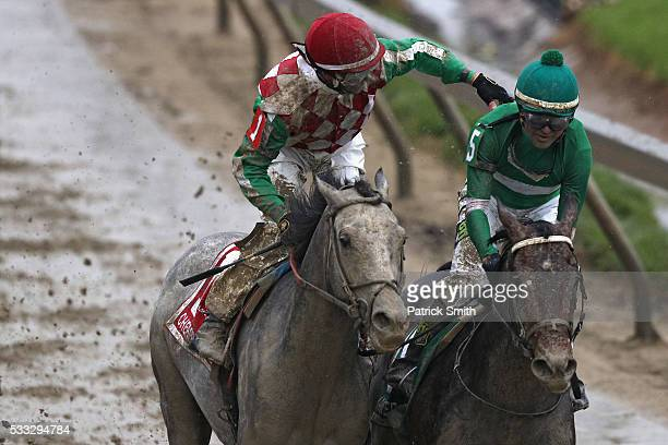 Jockey Corey Lanerie of Cherry Wine celebrates with jockey Kent Desormeaux of Exaggerator after Exaggerator crossed the finish line to win the 141st...