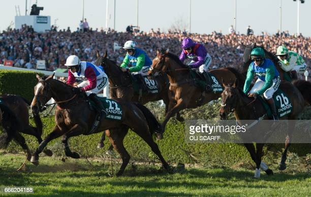 TOPSHOT Jockey Derek Fox rides One for Arthur negotiates the water jump on their way to winning the Grand National horse race on the final day of the...