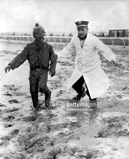Jockey Dick Morreale is assisted from the track after he and his mount Tempest fell in the stretch Fort Erie Ontario April 26 1961 They skidded 65...