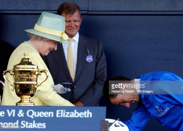 Jockey Frankie Dettori bows in front of Britain's Queen Elizabeth II duringt the presentation ceremony after winning The King George VI And Queen...