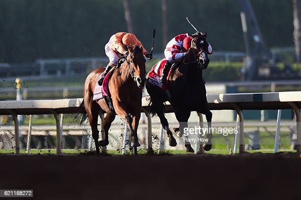 Jockey Gary Stevens aboard Beholder races alongside jockey Mike Smith aboard Songbird to the finish line in the Longines Breeders' Cup Distaff during...