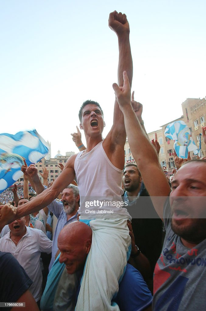 Jockey Giovanni Atzeni, also known as Tittia with members of the Contrada dell`Onda after the victory in the annual Palio dell'Assunta horse-race on August 16, 2013 in Siena, Italy. The Palio races in Siena, in which riders representing city districts compete,and takes place twice a year in the summer in a tradition that dates back to 1656.