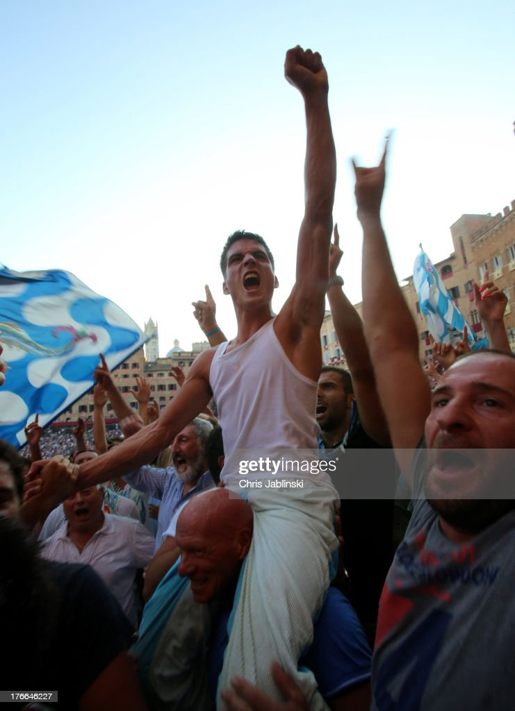 Jockey Giovanni Atzeni, known as Tittia, celebrates with his fans after winning the Palio dell'Assunta horse-race at Piazza del Campo square on August 16, 2013 in Siena, Italy. The Palio races in Siena, in which riders representing city districts compete, and takes place twice a year in the summer in a tradition that dates back to 1656.