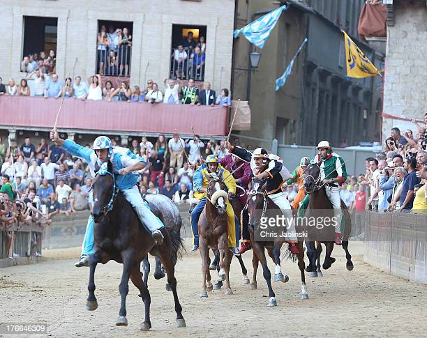 Jockey Giovanni Atzeni known as Tittia rides his horse bareback on his way to winning the Palio dell'Assunta horserace at Piazza del Campo square on...
