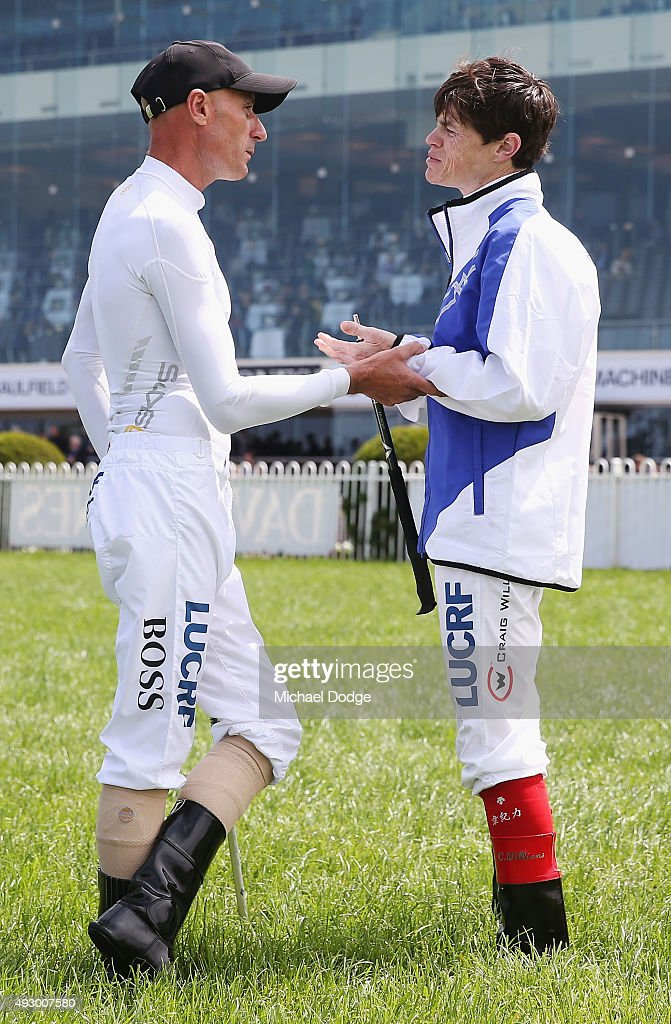 Jockey Glen Boss (L) grabs fellow Craig Williams when talking on the course proper before Race 1 during Caulfield Cup Day at Caulfield Racecourse on October 17, 2015 in Melbourne, Australia.