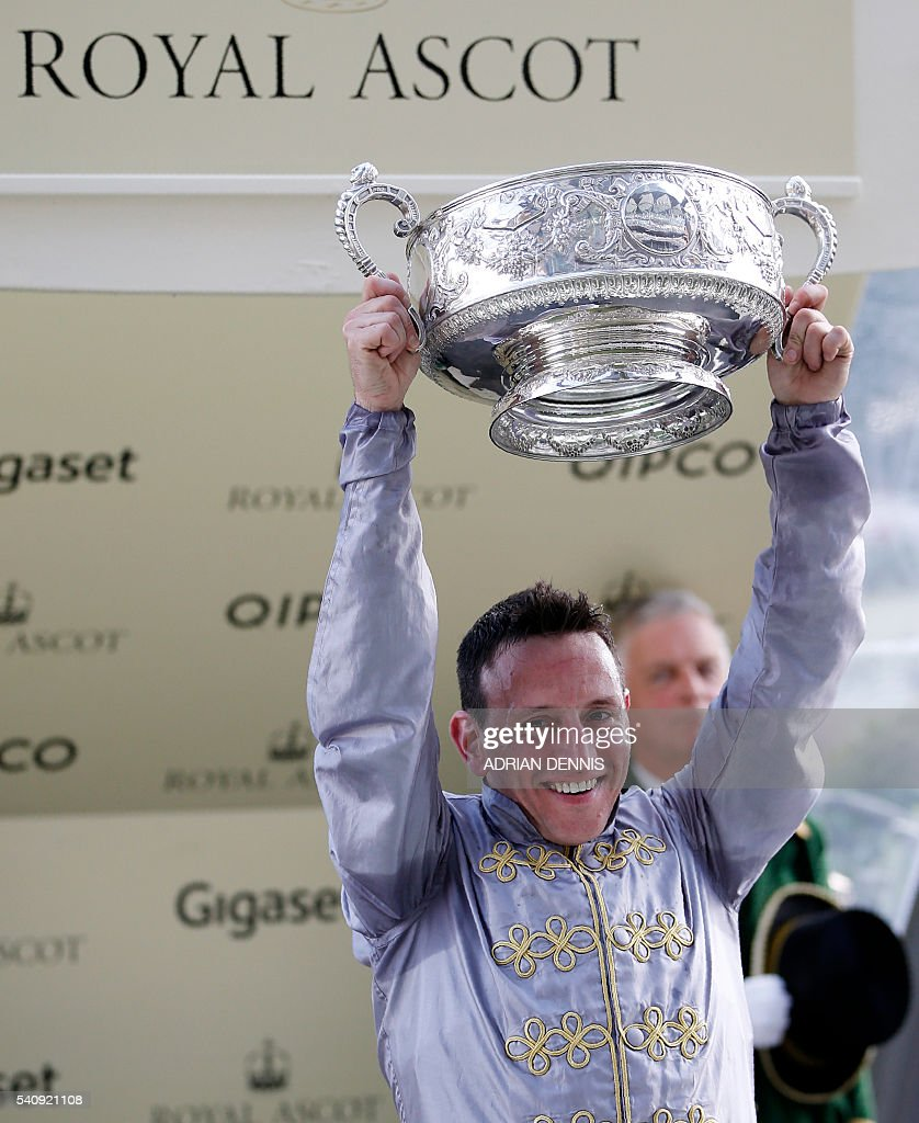 Jockey Gregory Benoist hold trophy after riding Qemah to victory to win The Coronation Stakes group 1 race during day four at Royal Ascot horse...