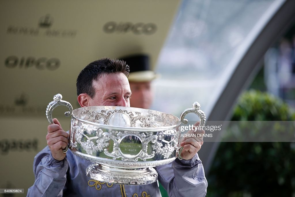 Jockey Gregory Benoist kisses the trophy after riding Qemah to victory to win The Coronation Stakes group 1 race during day four at Royal Ascot horse...