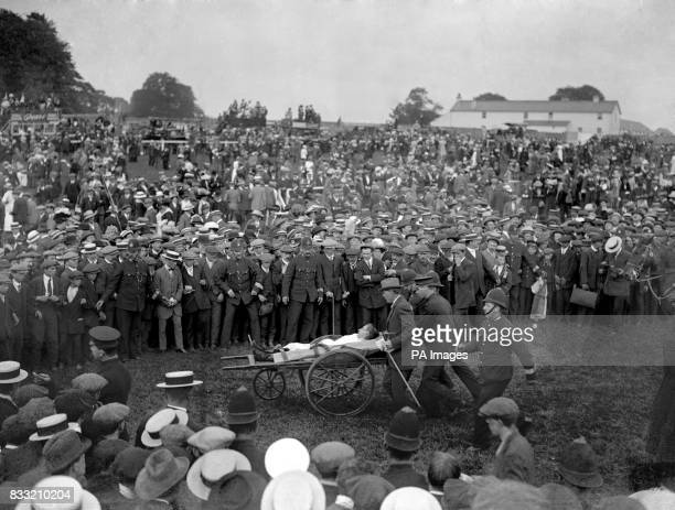 Jockey Herbert Jones is carried away on a stretcher after suffering a mild concussion and a fractured rib after suffragette Emily Davison threw...