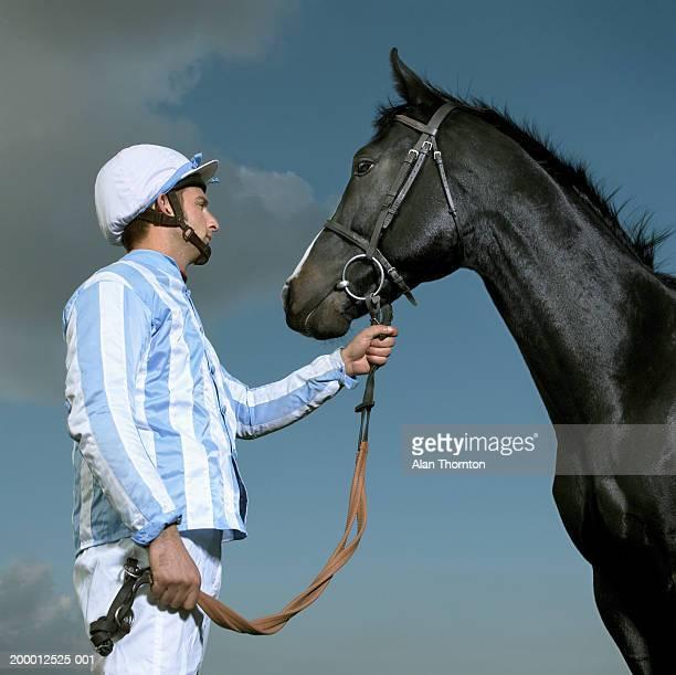 Jockey holding horse's reins, profile