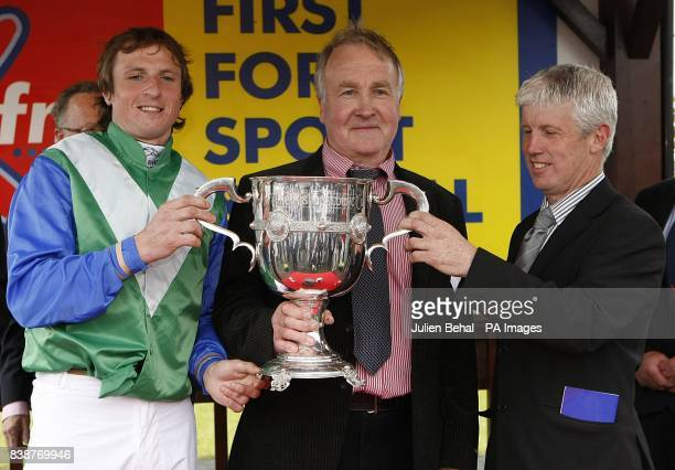 Jockey Jamie Codd celebrates with the trophy and trainer J P Dempsey after winning the KFM Hunters Chase for the Bishopscourt Cup on The Baler