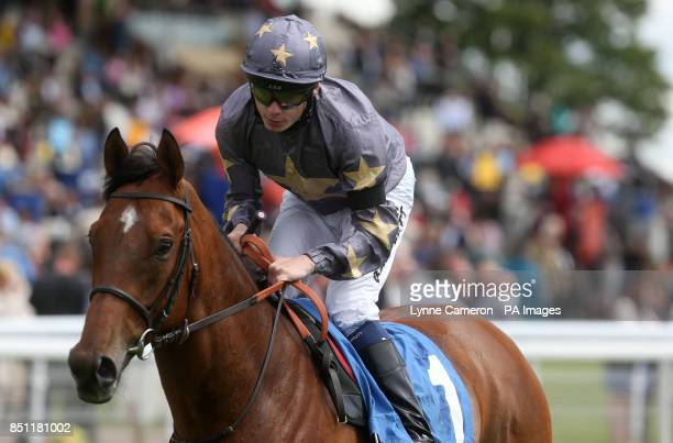 Jockey Jamie Spencer wears a black armband as he wins The Jigsaw Sponsorship Services Stakes on Montaser at York Racecourse York