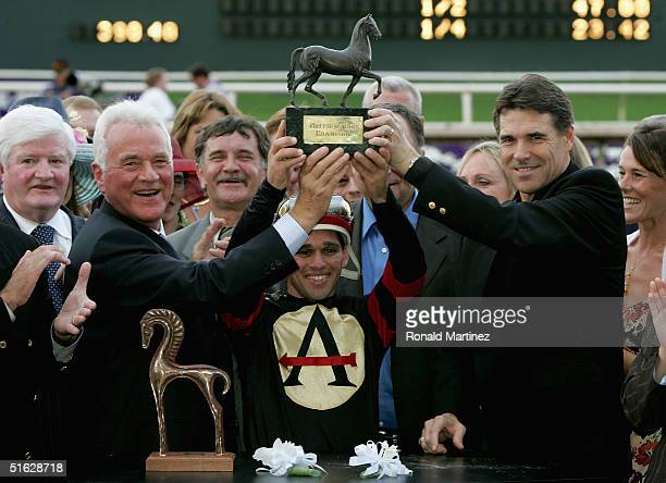 Jockey Javier Castellano holds the trophy with Governor of Texas Rick Perry trainer of Ghostzapper Robert J Frankel and owner Frank Stronach in the...