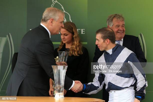 Jockey Jim Crowley receives the trophy from the Duke of York after his horse Ulysses won the Juddmonte International Stakes during Juddmonte...