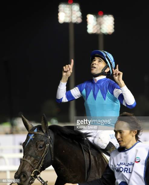 Jockey Joao Moreira celebrates after leading Vivlos to win the Dubai Turf at the Dubai World Cup in the Meydan Racecourse on March 25 2017 in Dubai /...