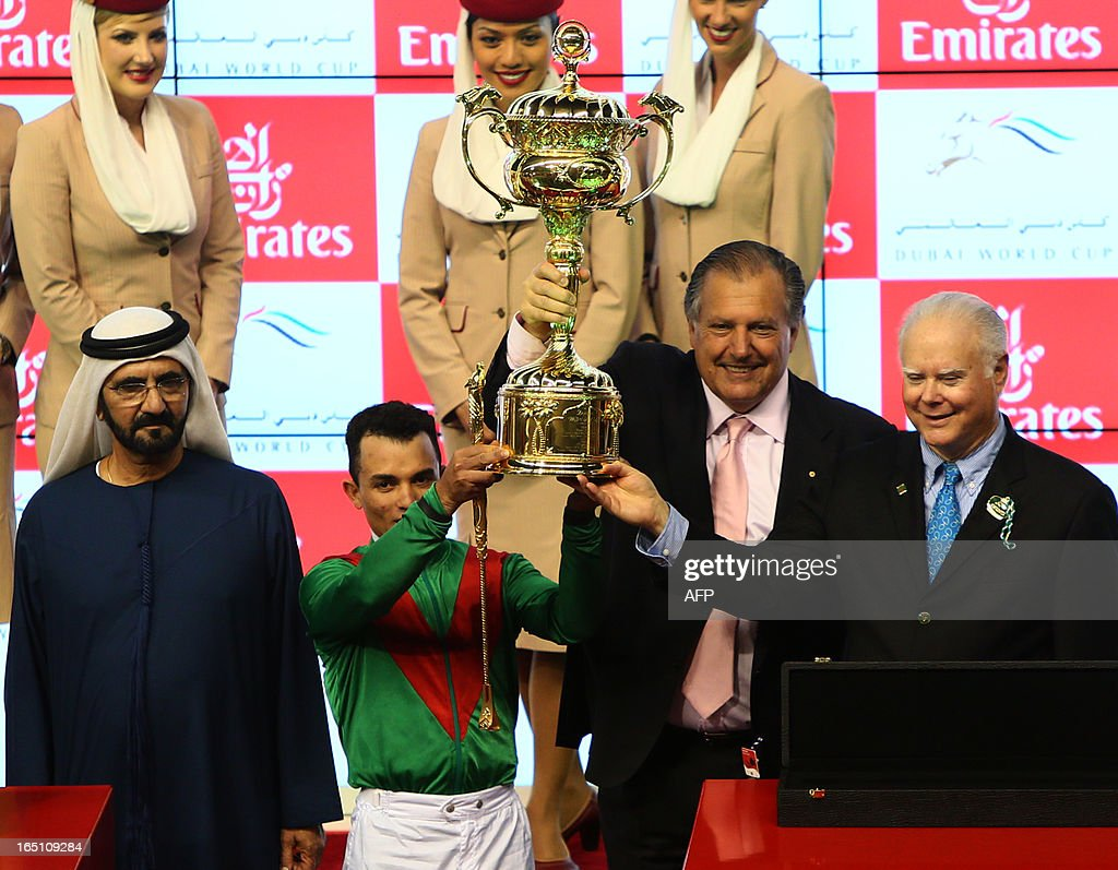 Jockey Joel Rosario and the Austrailain owners (R) of Animal Kingdom, raise the trophy along with the ruler of Dubai Sheikh Mohammed Bin Rashid al-Maktoum (L) after winning the $10 million Dubai World Cup, the world's richest race, at Meydan race track in Dubai March 30, 2013. The 2011 Kentucky Derby winner (11/2), trained by American Graham Motion and ridden by Rosario, beat home English raider Red Cadeaux by two lengths while another English-trained runner Planteur was third.