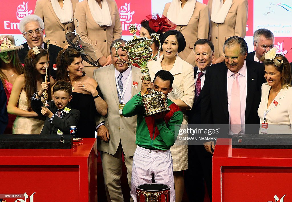 Jockey Joel Rosario (C) kisses the trophy after leading Animal Kingdom to win the Dubai World Cup, the world's richest races, as the Australian owners of the horse and their family celebrate, at Meydan race track in Dubai March 30, 2013. The 2011 Kentucky Derby winner (11/2), trained by American Graham Motion and ridden by Joel Rosario, beat home English raider Red Cadeaux by two lengths while another English-trained runner Planteur was third.