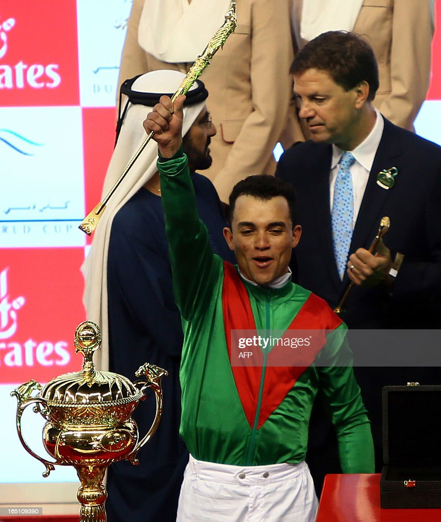 Jockey Joel Rosario raise the golden riding crop as he stands next to the trophy after leading Animal Kingdom to win the $10 million Dubai World Cup, the world's richest race, at Meydan race track in Dubai March 30, 2013. Animal Kingdom, the 2011 Kentucky Derby winner (11/2), trained by American Graham Motion and ridden by Rosario, beat home English raider Red Cadeaux by two lengths while another English-trained runner Planteur was third.