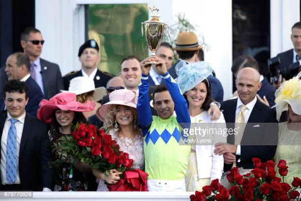 Jockey John Velazquez holds up the trophy in the winner's circle after winning the 143rd running of the Kentucky Derby at Churchill Downs on May 6...