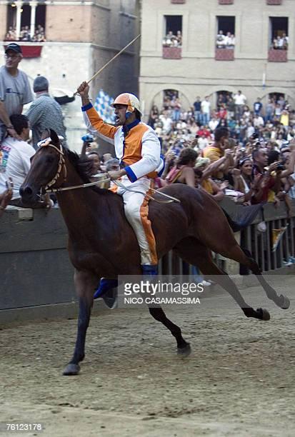 Jockey Jonathan Bartoletti named Scompiglio of Leocorno parish celebrates after winning the Palio horse race in the Piazza del Campo in Siena 16...
