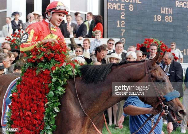 Jockey Kent Desormeaux carries a bed of roses as he rides Real Quiet around the winner's circle after winning 124th running of the Kentucky Derby 02...