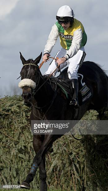 Jockey Leighton Aspell on horse 'Many Clouds' jumps the final fence on his way to winning the Grand National horse race on the final day of the Grand...