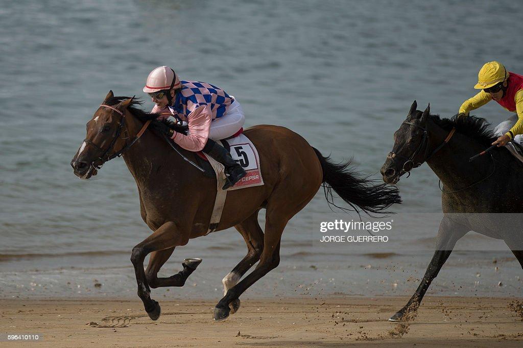 Jockey Lopez competes against J Gilbert during the annual beach horse race at Sanlucar de Barrameda near Cadiz on August 27 2016 / AFP / JORGE...