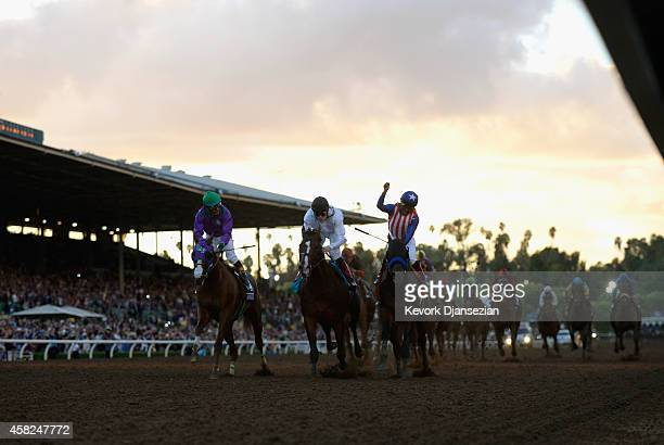 Jockey Martin Garcia atop Bayern celebrates winning the 2014 Breeders' Cup Classic ahead of second place finisher jockey Jamie Spencer atop Toast of...