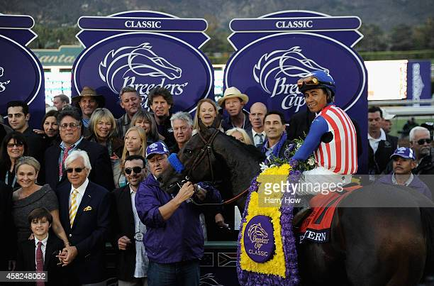Jockey Martin Garcia atop Bayern celebrates with his team in the winner's circle after the 2014 Breeders' Cup Classic at Santa Anita Park on November...