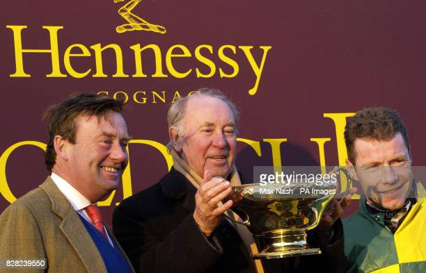 Jockey Mick Fitzgerald trainer Nicky Henderson and owner Trevor Hemmings hold up the Hennessy Gold Cup after Mick Fitzgerald won the race on...