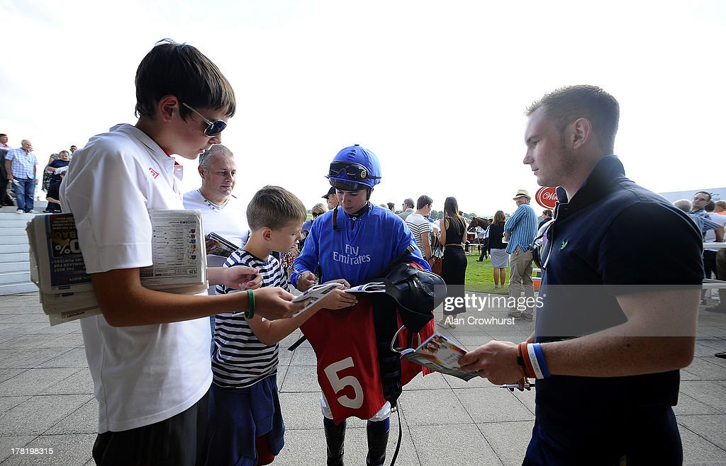 Jockey Mickael Barzalona signs autographs for fans at Epsom racecourse on August 27, 2013 in Epsom, England.