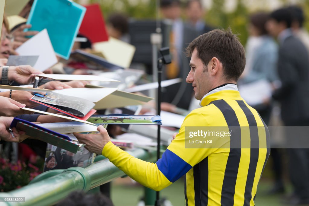 Jockey Mirco Demuro gives his autograph to Japanese racing fans at Nakayama Racecourse on March 6, 2016 in Funabashi, Chiba, Japan.
