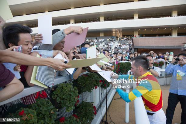 Jockey Mirco Demuro gives his autograph to Japanese racing fans at Sapporo Racecourse on August 27 2016 in Sapporo Hokkaido Japan