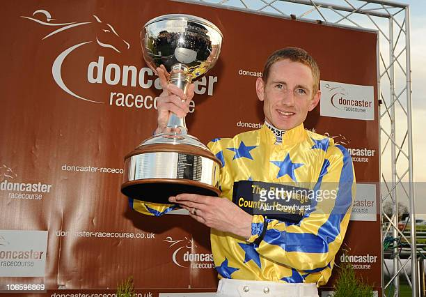 Jockey Paul Hanagan lifts the trophy after winning the flat jockeys championship by riding the most winners in the season at Doncaster racecourse on...