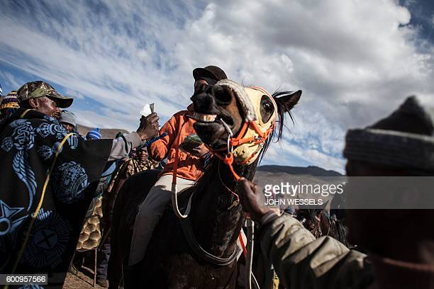A jockey receives his reward after the race as a man struggle to control his horse on July 16 2016 in Semonkong Horseracing in the mountain kingdom...