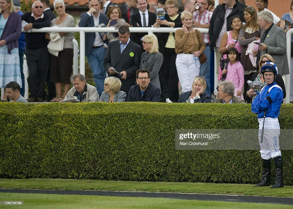Jockey Richard Hills waits for his mount at Newmarket racecourse on September 24, 2011 in Newmarket, England.