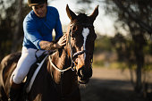 Male jockey riding horse at barn
