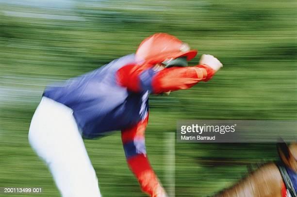 Jockey riding racehorse, arm raised, close-up (blurred motion)