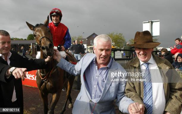 Jockey Ruby Walsh on Quevega is lead into the winner's enclosure by owners Ger O'Brien and Sean Deane after winning the Ladbrokescom World Series...
