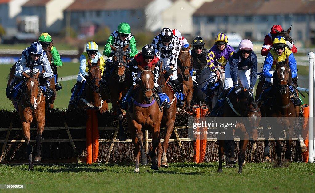 Jockey Ryan Mania (Blue & Yellow hat), riding Karinga Dandy competes in the Befriend Johnnie Delta Racing On Facebook Handicap hurdle race (4:25), at Ayr racecourse on April 19, 2013 in Ayr, Scotland.