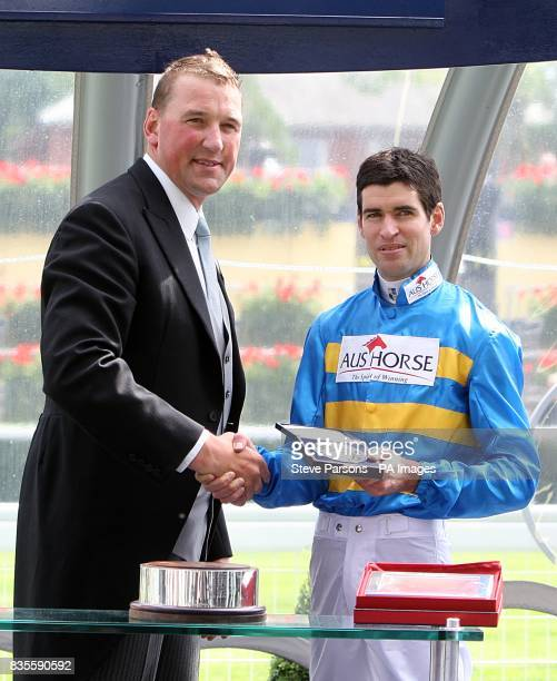 Jockey Steven Arnold collects his trophy from Matthew Pinsent after Scenic Blast wins the King's Stand Stakes at Ascot