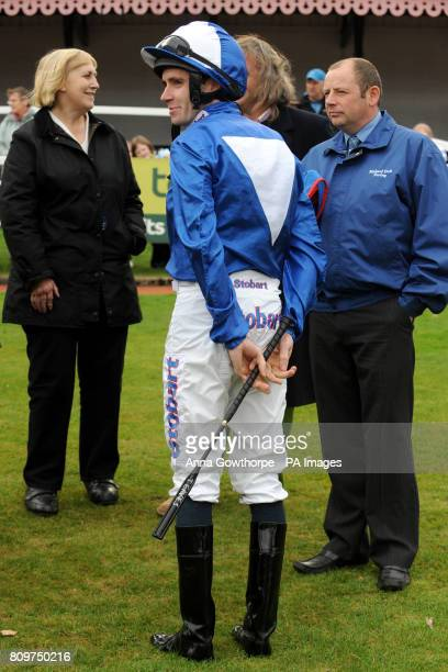 Jockey Tom Eaves holds his whip in the parade ring
